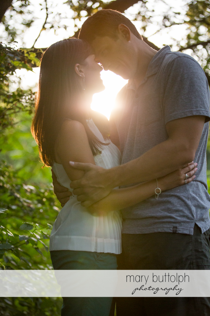 Couple embrace as the sun sets in the woods at Skaneateles Lodge at Welch Allyn Engagement