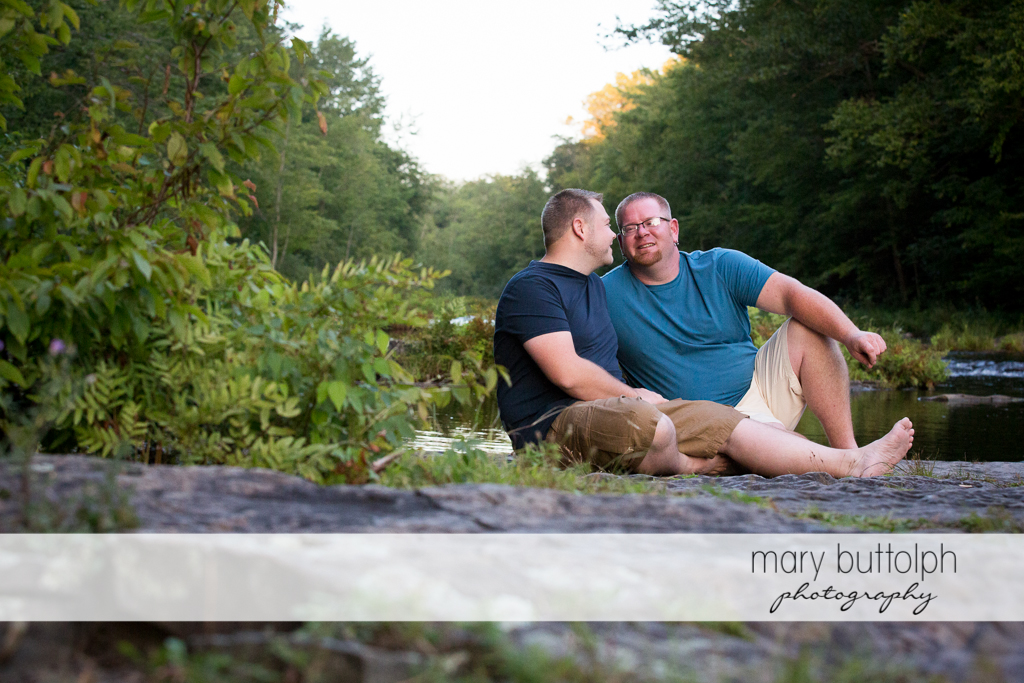 same sex couple take a break at the riverbank at Salmon River Falls Engagement Session