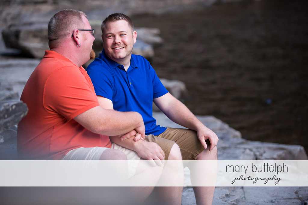 Same sex couple relax by the river at Salmon River Falls Engagement