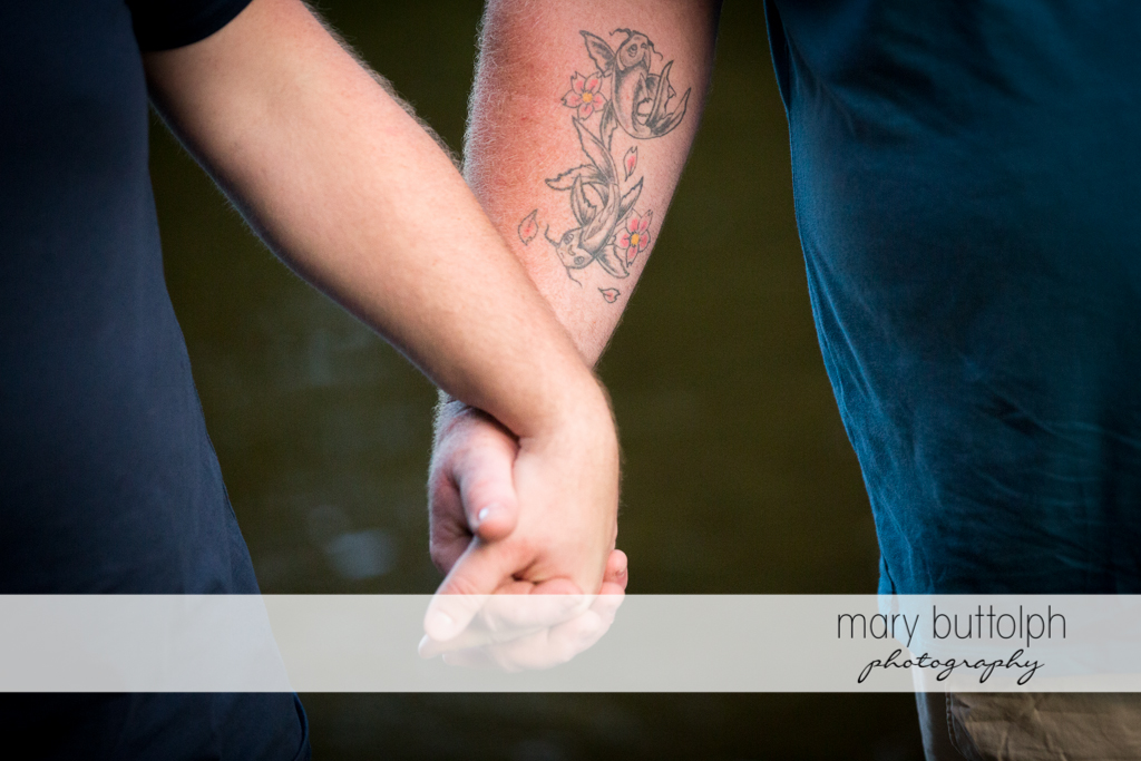Same sex couple hold hands in the river at Salmon River Falls Engagement