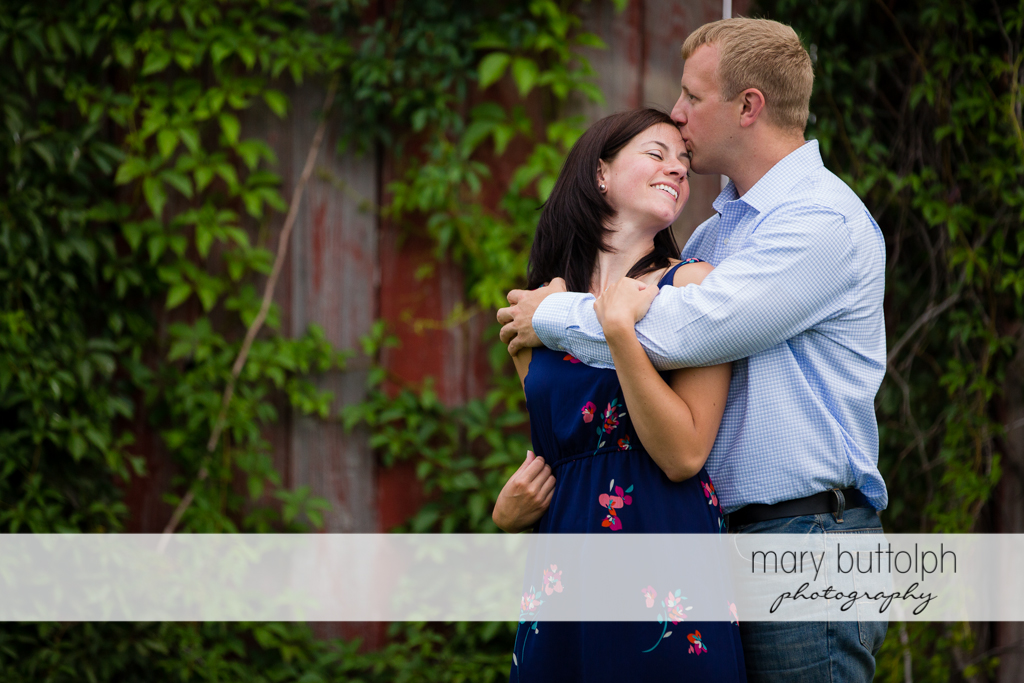 Couple pose near a wooden structure at Skaneateles Farm Engagement
