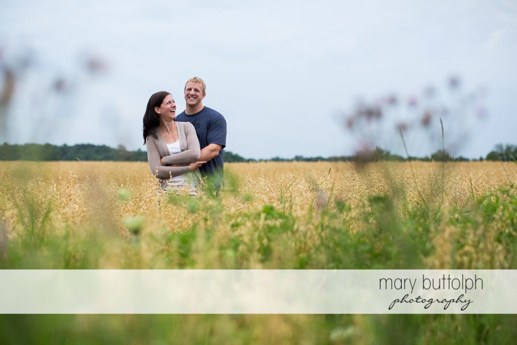 Couple pose in the field at Skaneateles Farm Engagement