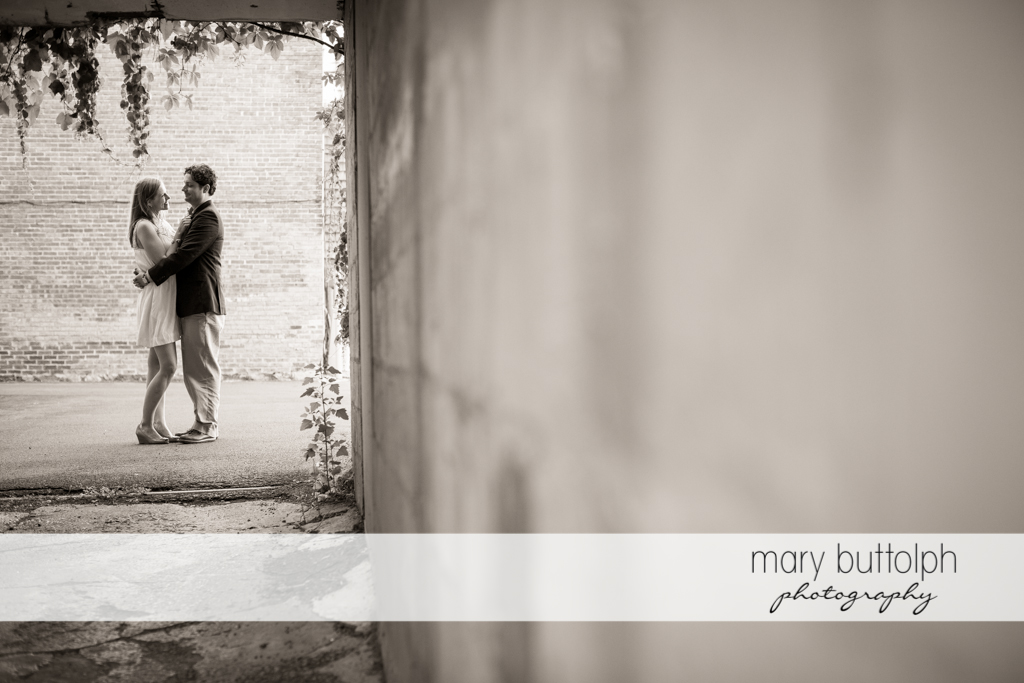 Couple stand near a brick wall at Skaneateles Engagement