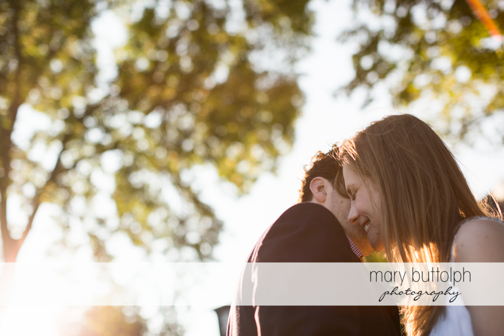 Couple share a quiet moment under the trees at Skaneateles Engagement
