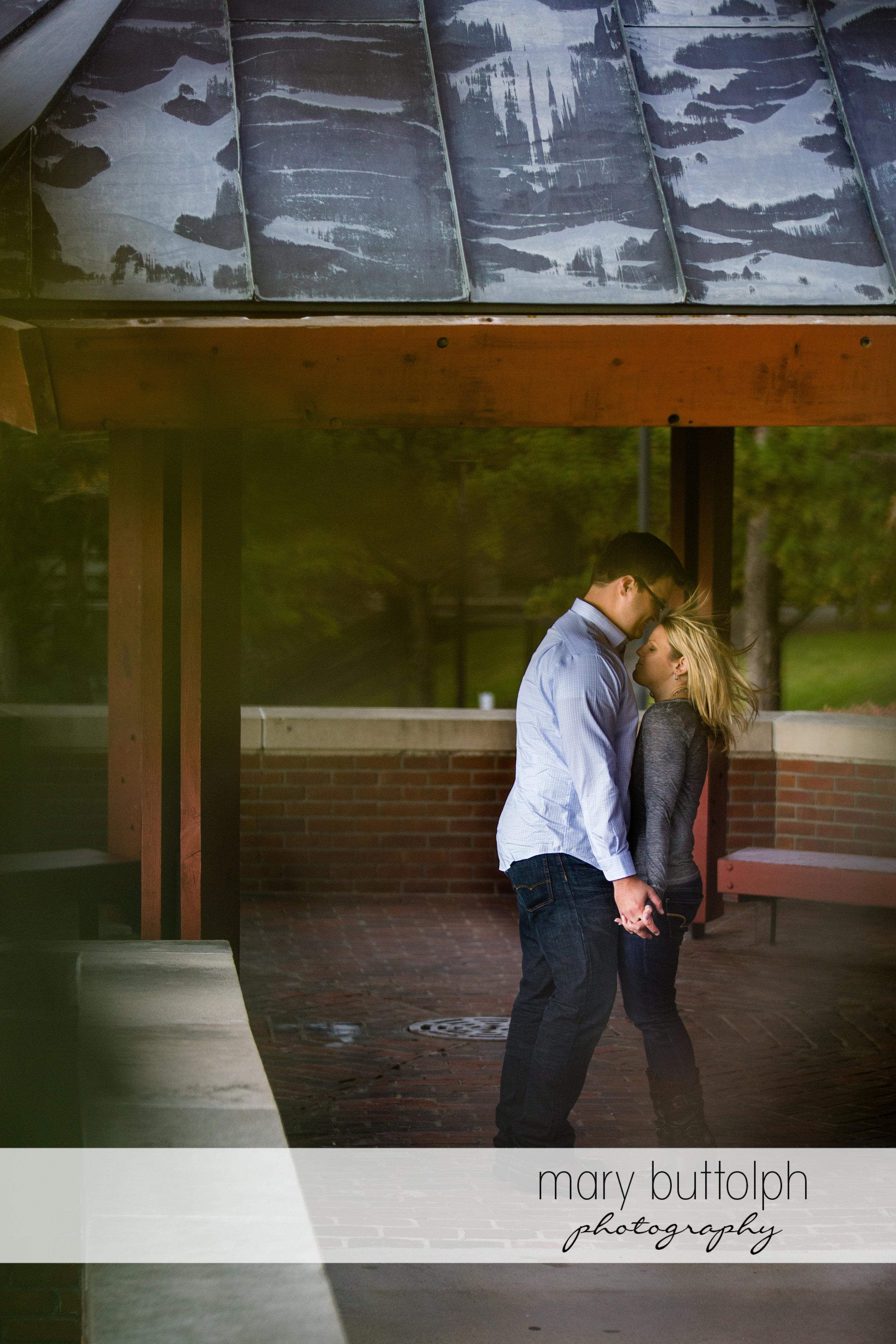 Couple enjoy the shade near a brick wall at SUNY Geneseo Engagement