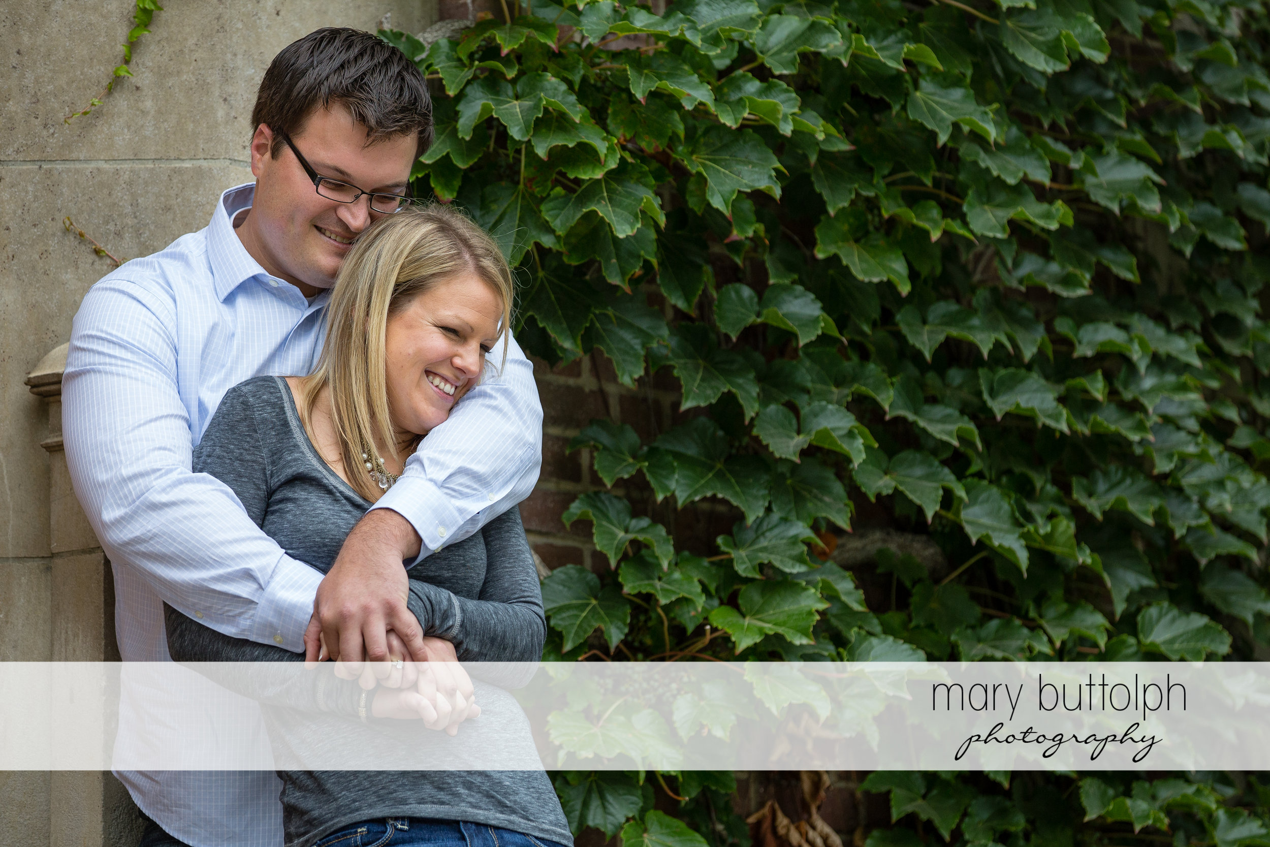 Couple lean on a wall partly covered with plants at SUNY Geneseo Engagement