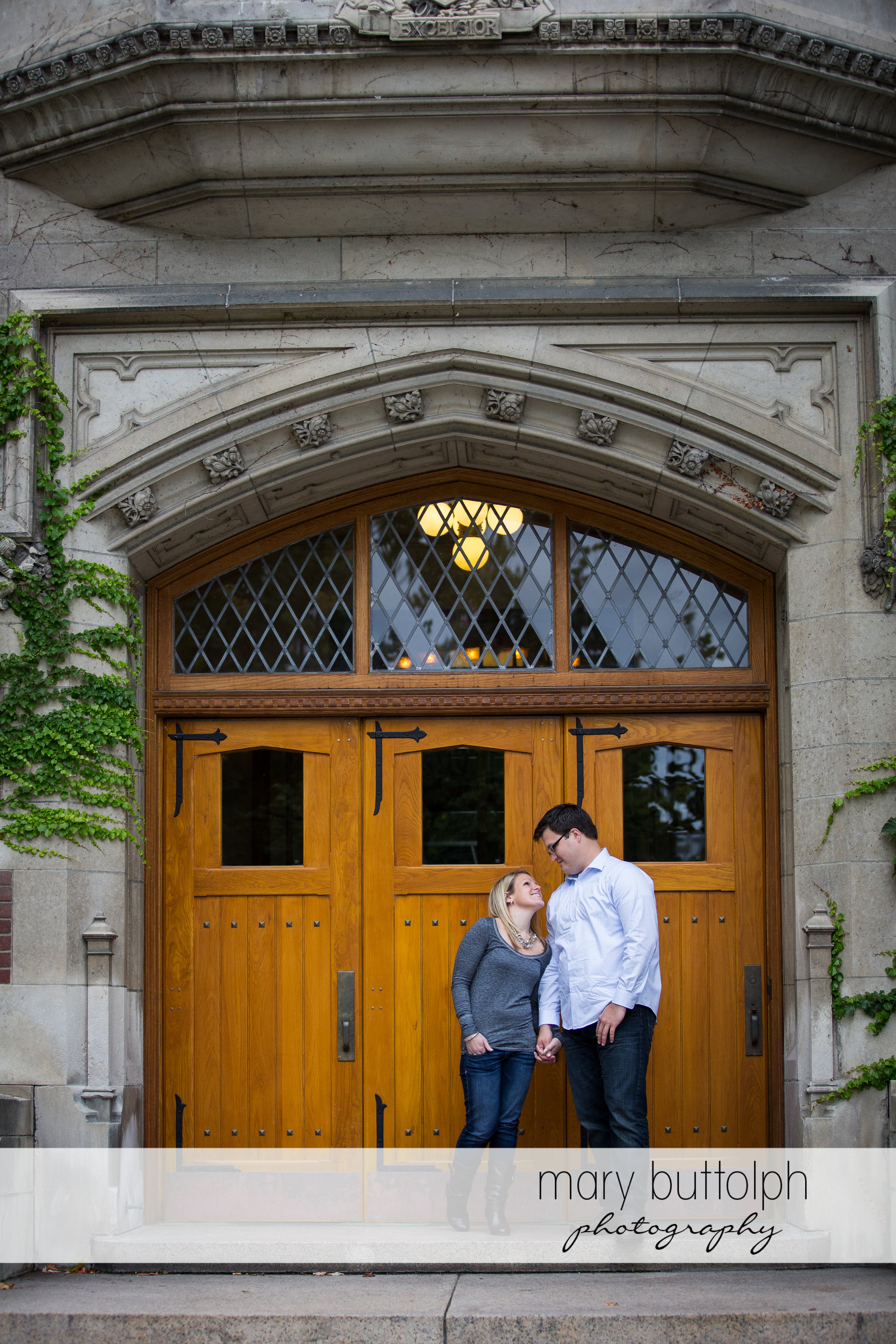 Couple pose in front of an old building at SUNY Geneseo Engagement