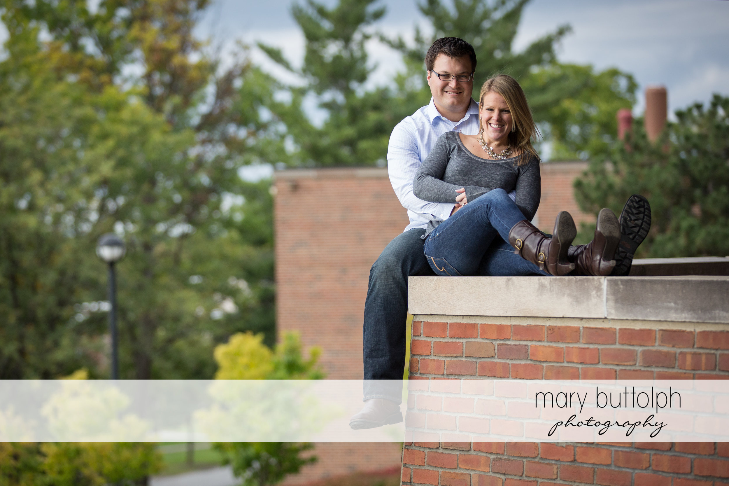 Couple sit on a brick divider at SUNY Geneseo Engagement