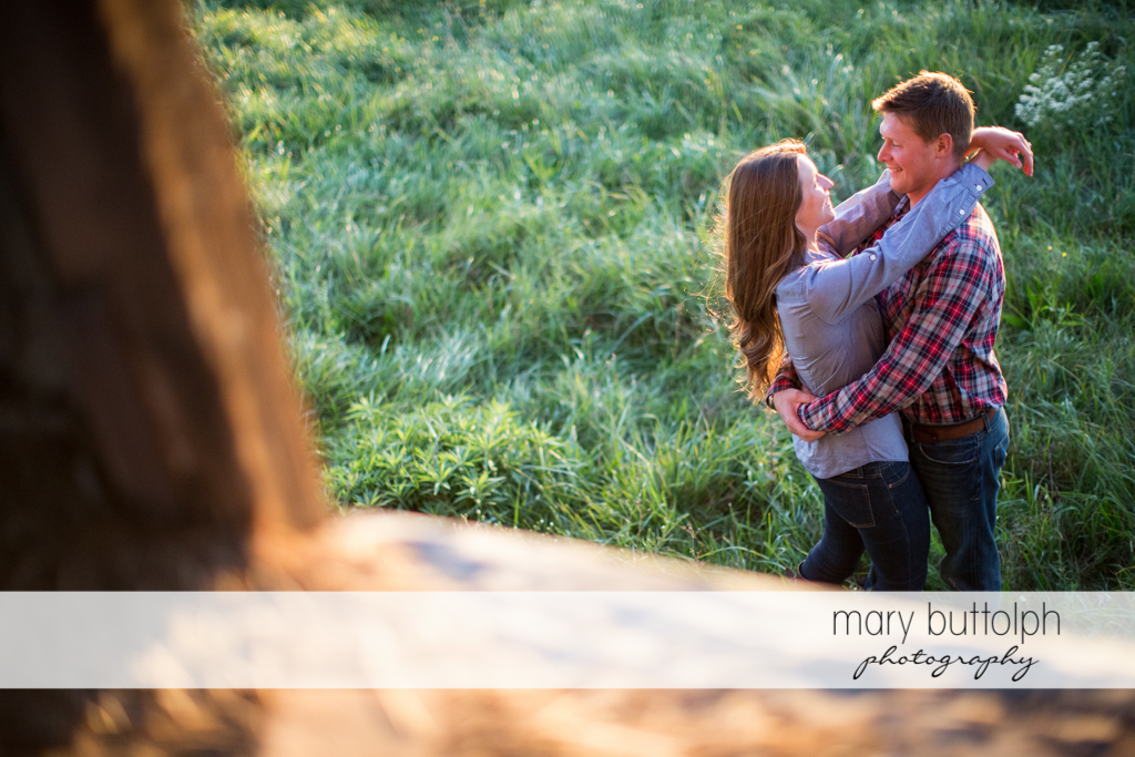 Couple embrace near a barn at Aurora Engagement