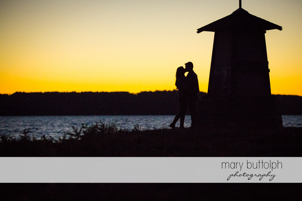 Couple kiss in the sunset near the lake at Aurora Engagement