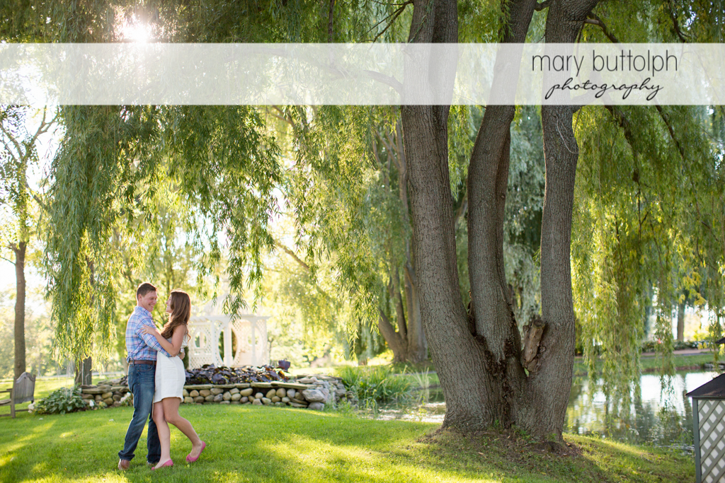 Couple embrace under a tress in the garden at Aurora Engagement