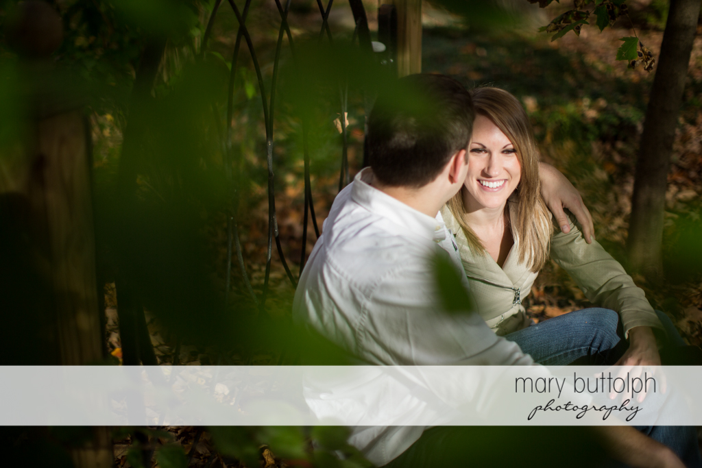 Couple rest in the woods at Skaneateles Engagement