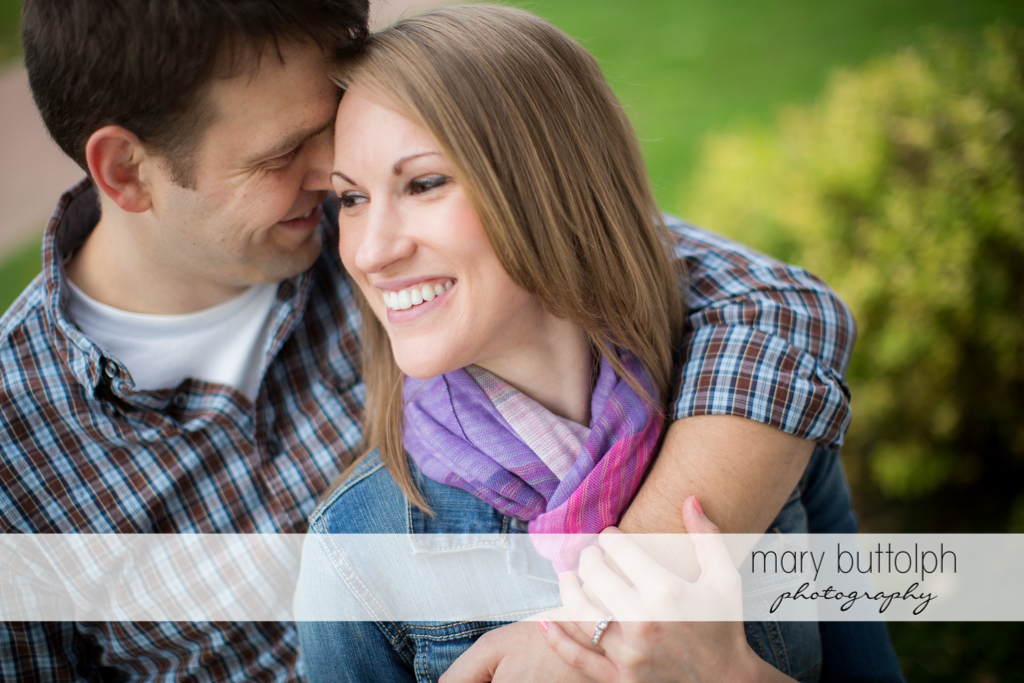 Couple share a tender moment in the woods at Skaneateles Engagement