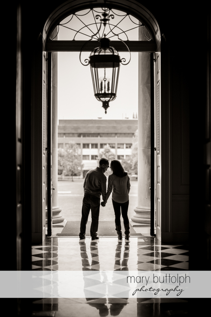 Couple stand at the entrance of a building at Syracuse University Engagement