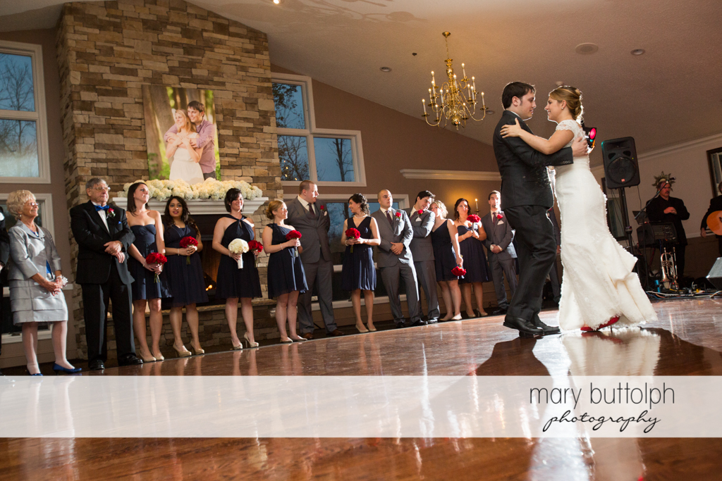Couple dance as the wedding party and guests look on at Traditions at the Links Wedding