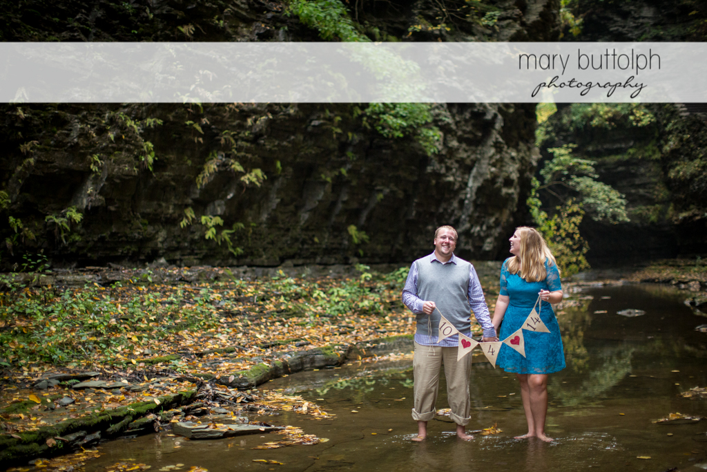 Couple wade in the stream as they show their wedding date at Watkins Glen Engagement