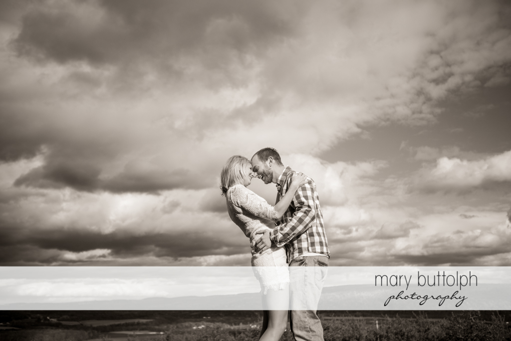 Couple in a dramatic black and white shot in the field at Beak & Skiff Apple Orchards Engagement