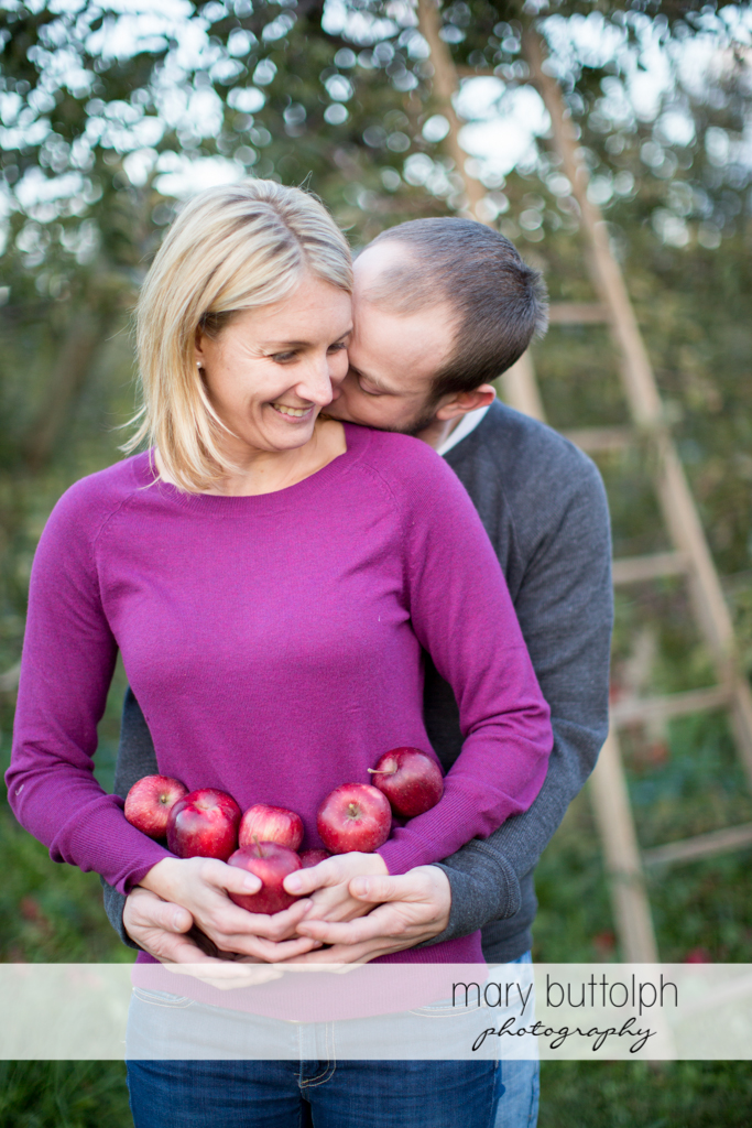 Couple with apples show their affection in the garden at Beak & Skiff Apple Orchards Engagement