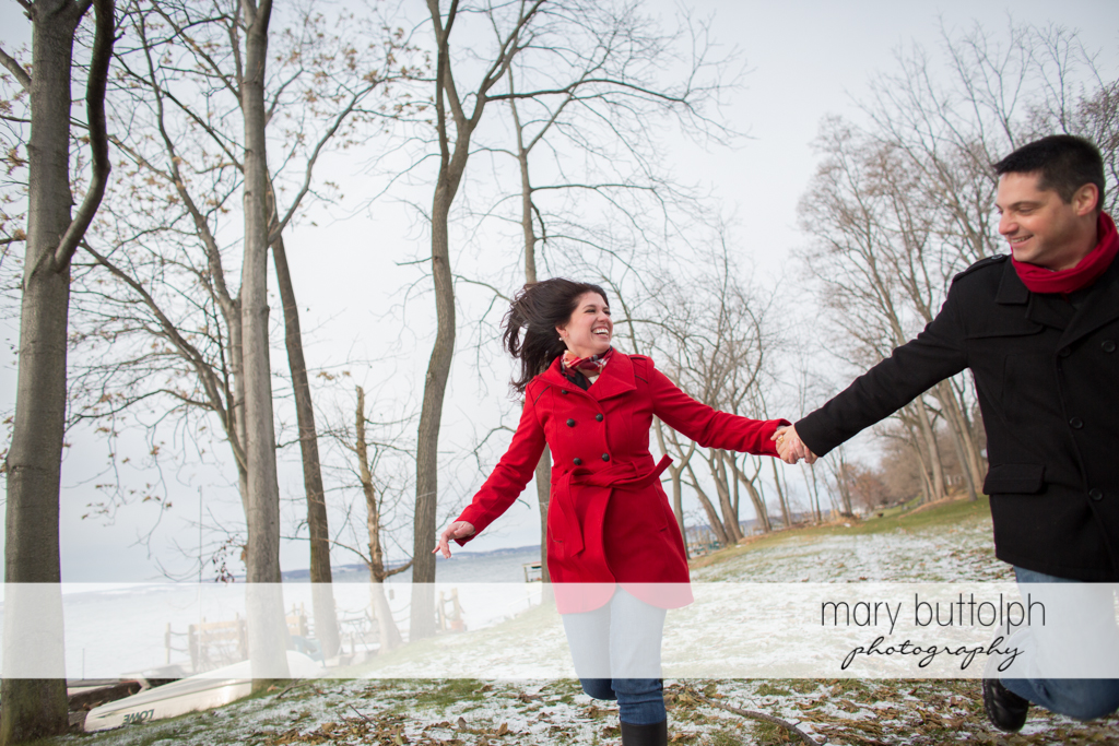 Couple brave the chilly weather as they pass by the lake at the Aurora Inn Engagement