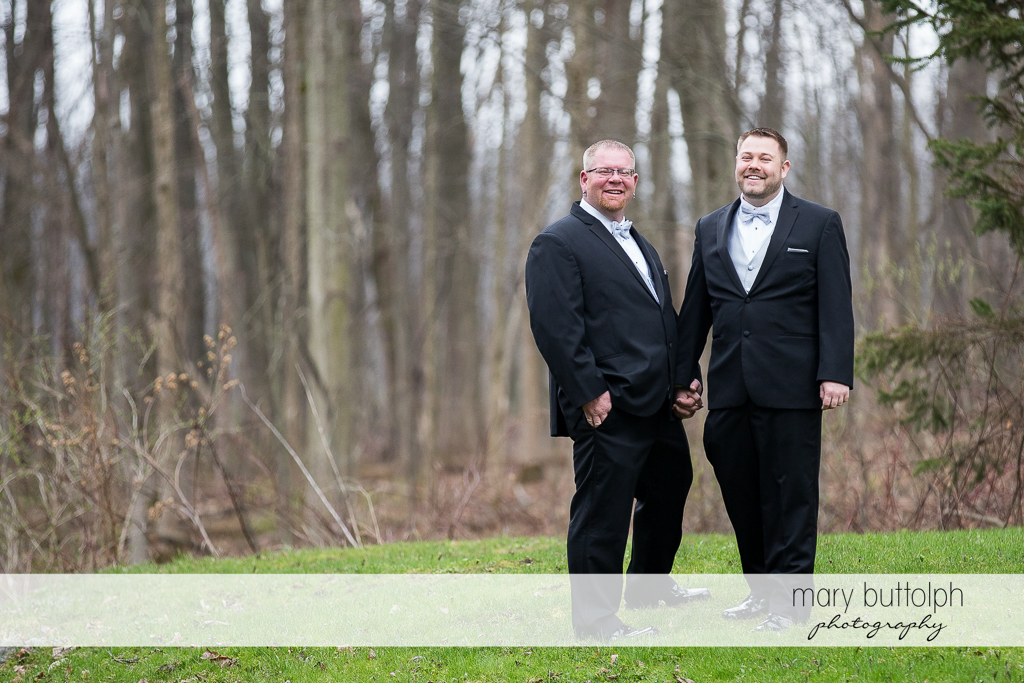 Same sex couple hold hands in the woods at Arrowhead Lodge Wedding