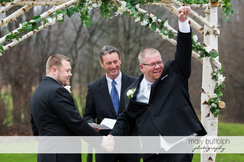 One of the groom raises his hand after the wedding at Arrowhead Lodge Wedding