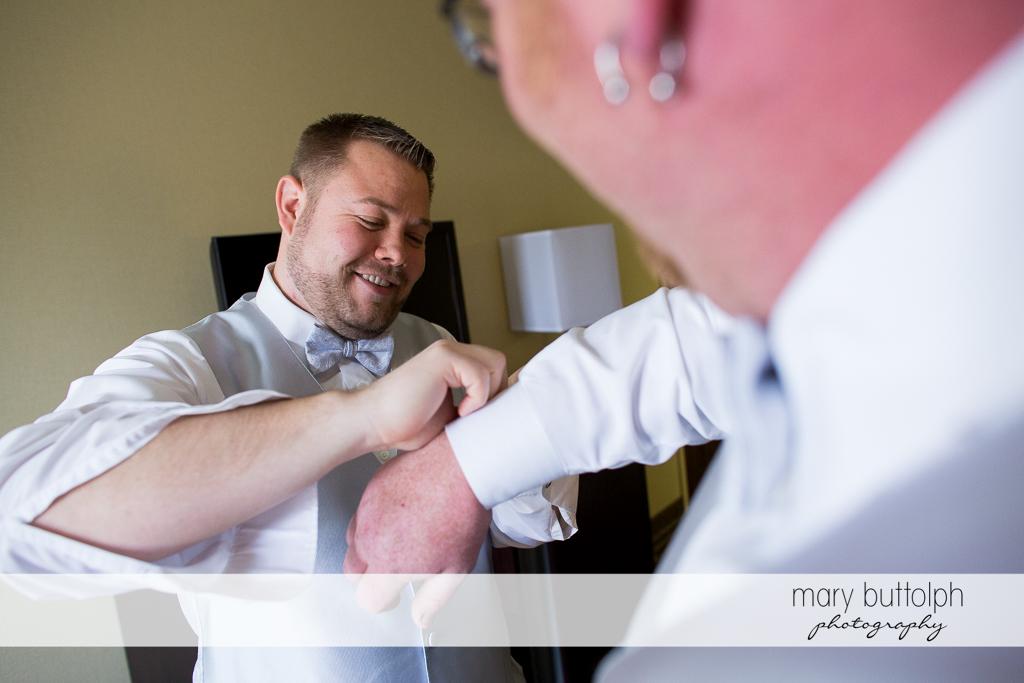 Same sex couple help each other dress at Arrowhead Lodge Wedding
