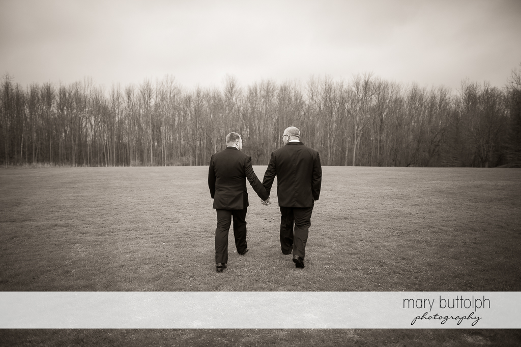 Same sex couple stroll in the woods at Arrowhead Lodge Wedding