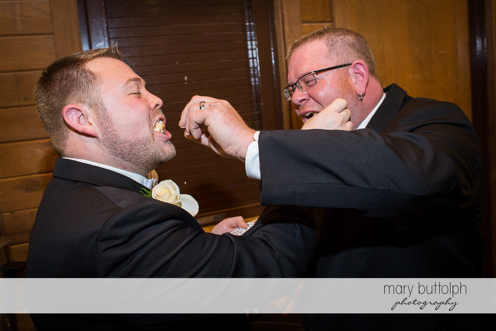 Same sex couple feed each other with cake at Arrowhead Lodge Wedding