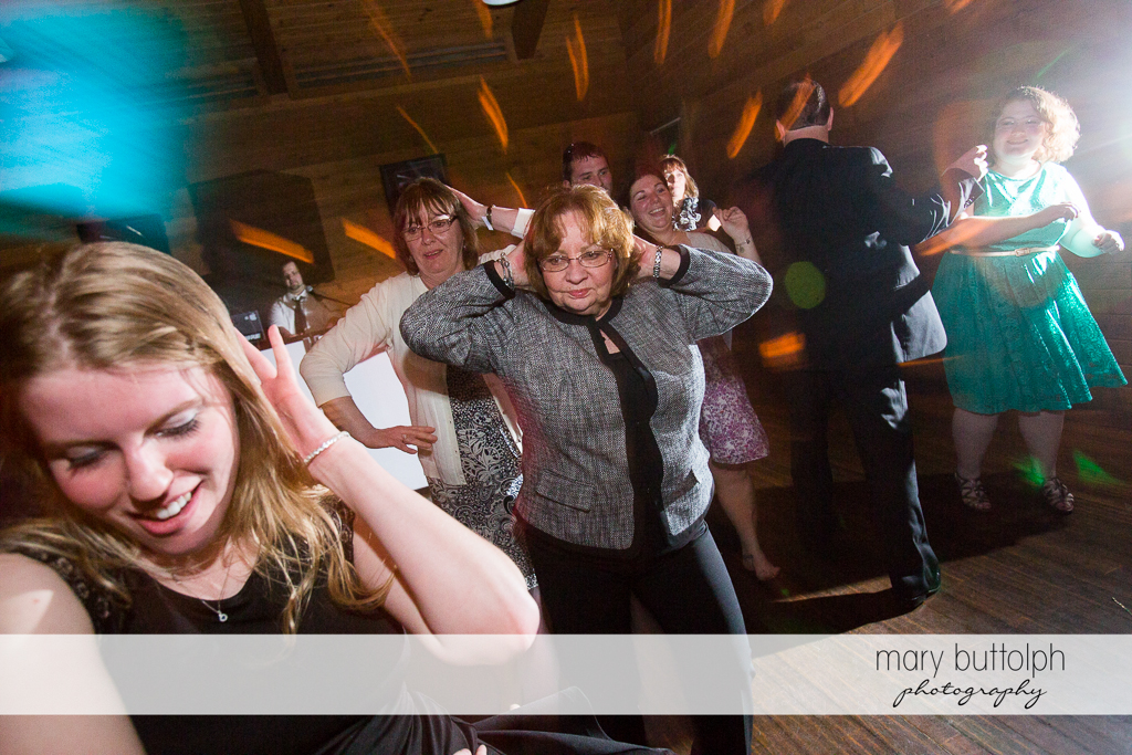 Same sex couple's guests party on the dance floor at Arrowhead Lodge Wedding