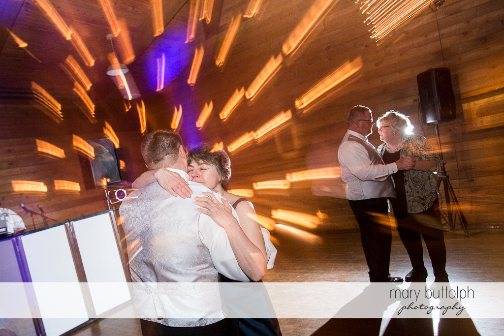 Same sex couple dance with guests at the wedding venue at Arrowhead Lodge Wedding