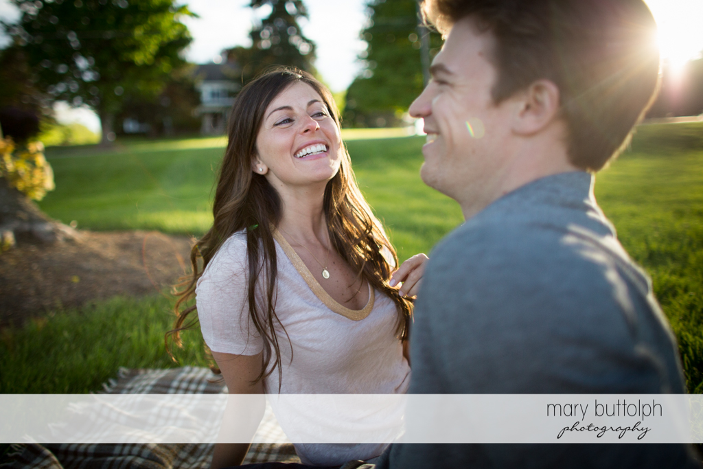 Couple sit on the grass in the garden at Skaneateles Engagement