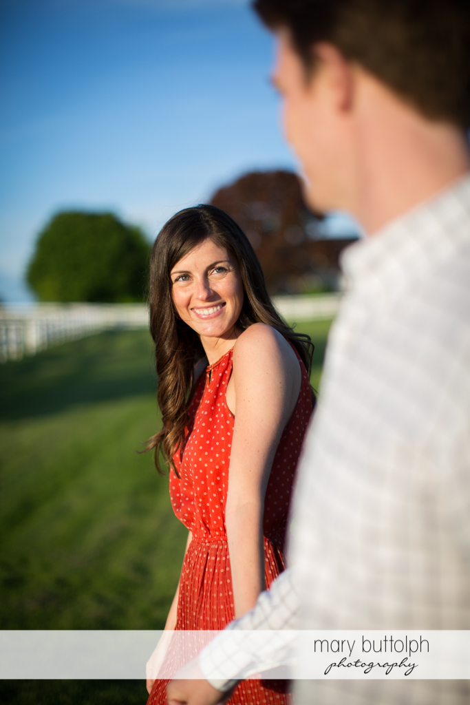 Woman looks at her companion while strolling in the meadow at Skaneateles Engagement