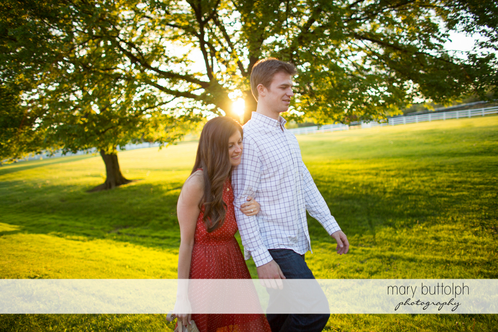 Couple pass by trees as they stroll in the garden at Skaneateles Engagement