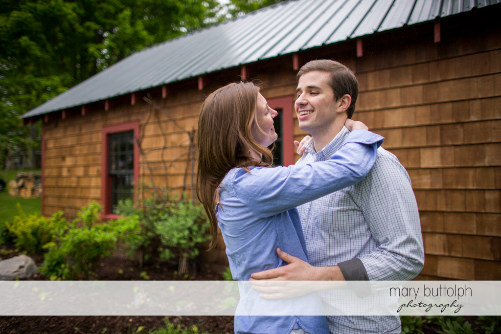 Couple embrace in front of a wooden house at the Hamilton Inn Engagement
