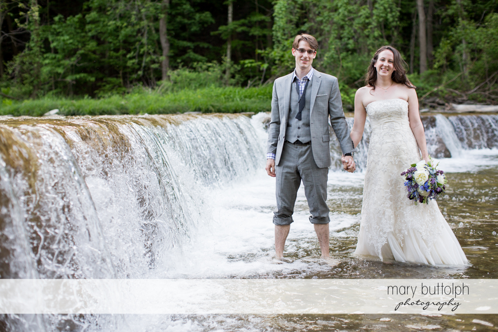 Couple holds hands while crossing the lake at Taughannock Falls Wedding