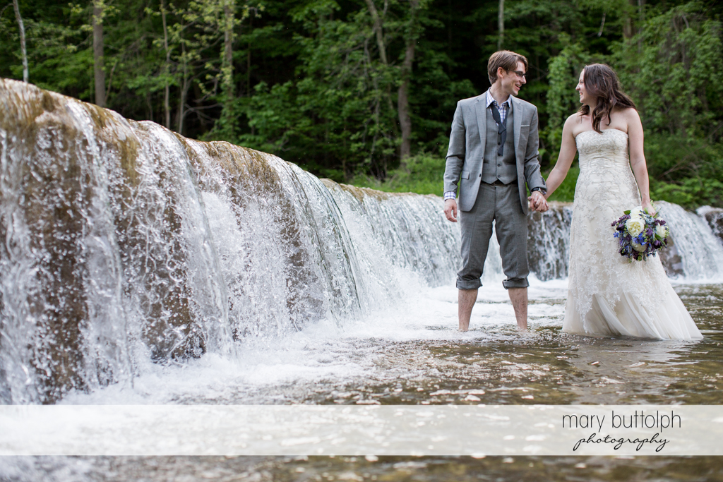 Couple face each other in the lake at Taughannock Falls Wedding
