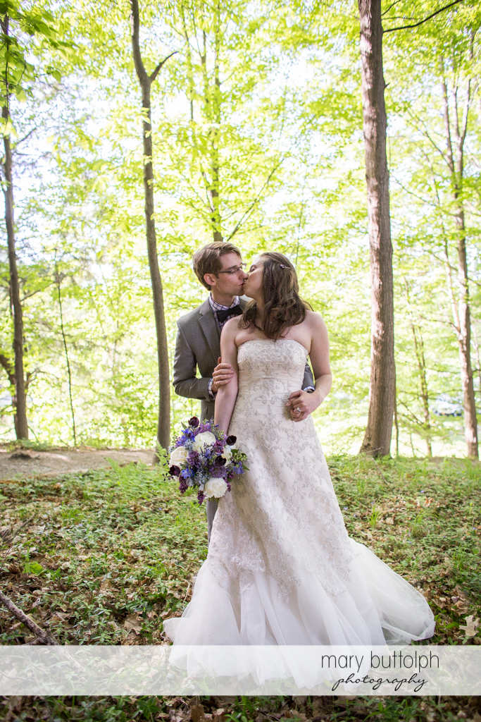 Couple kiss in the woods at Taughannock Falls Wedding