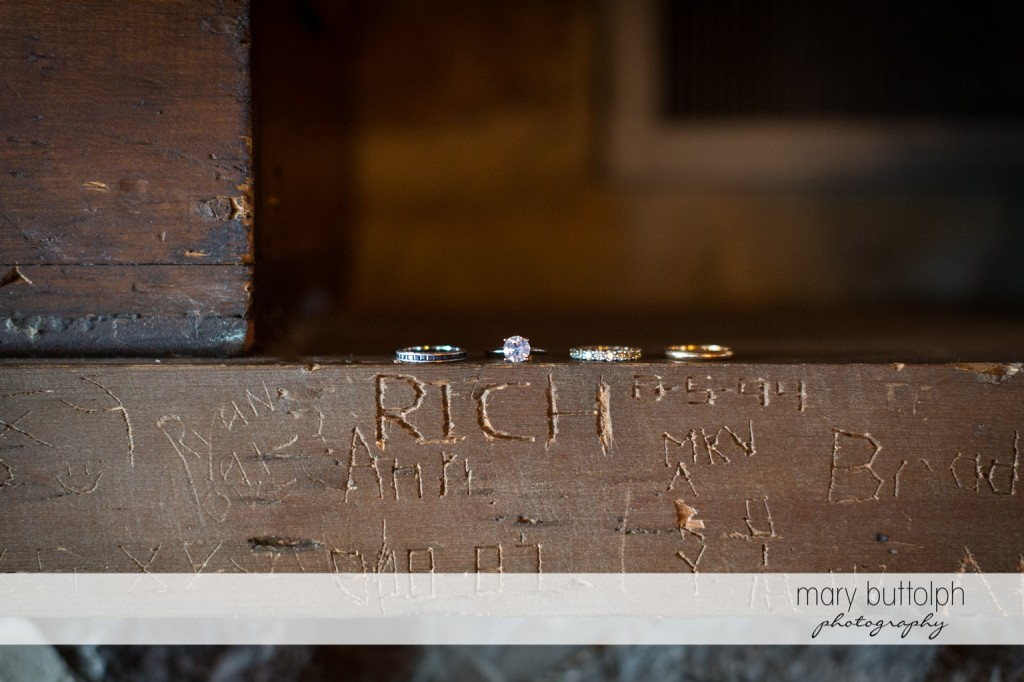 The couple's wedding rings on top of a wooden beam with the groom's name at Skaneateles Country Club Wedding