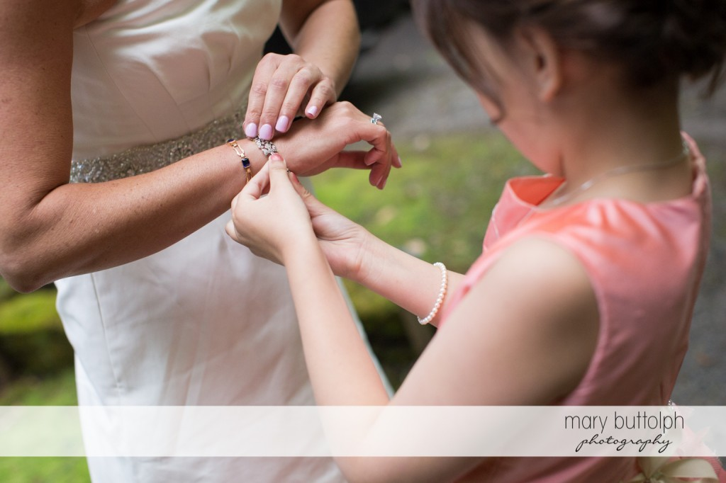 Young girl helps bride put on her bracelet at Skaneateles Country Club Wedding