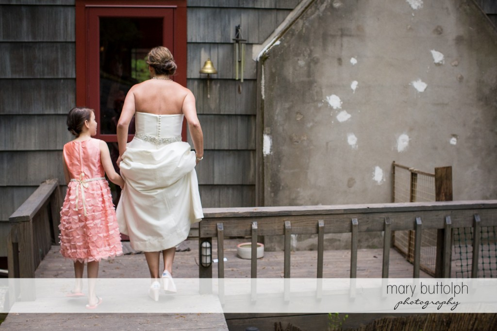 Bride and young girl make their way to a door at Skaneateles Country Club Wedding
