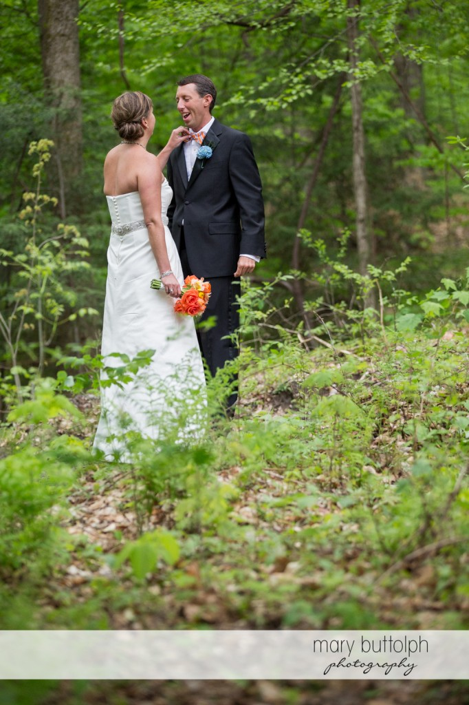 Bride fixes the groom's tie in the woods at Skaneateles Country Club Wedding