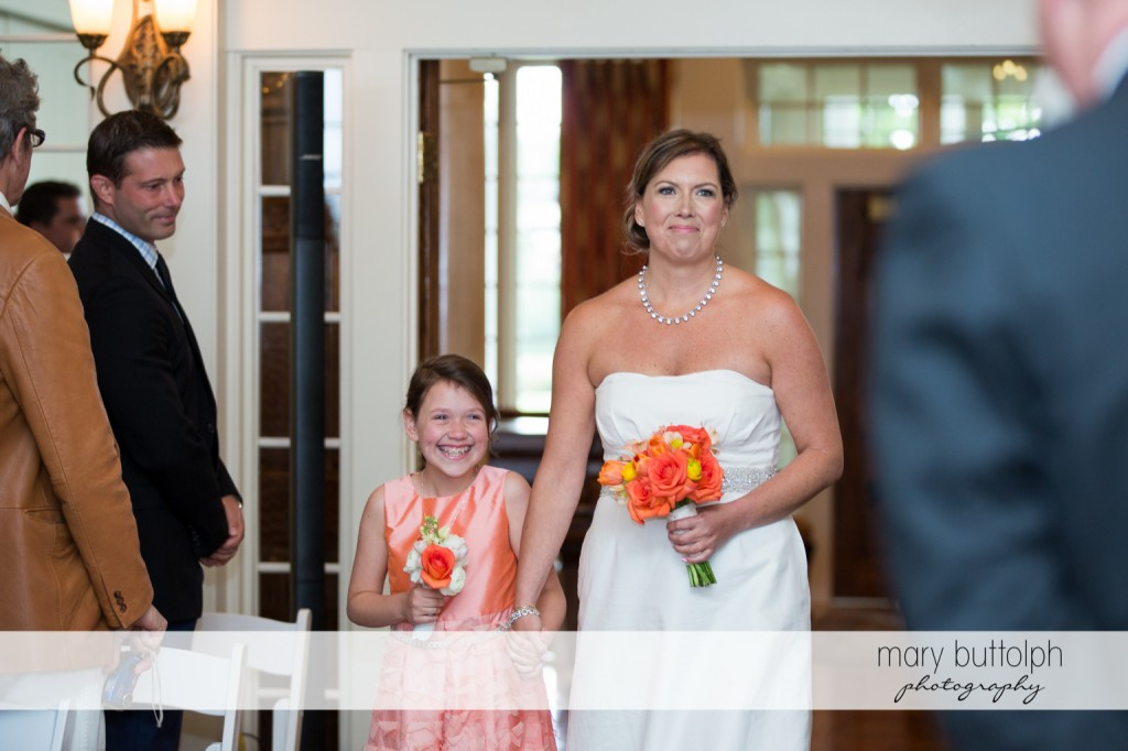 Bride and young girl with bouquets walk down the aisle at Skaneateles Country Club Wedding