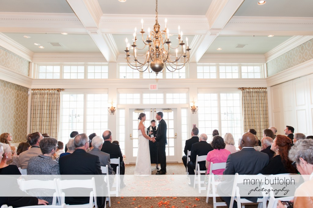Long shot of the couple in front of the priest at Skaneateles Country Club Wedding