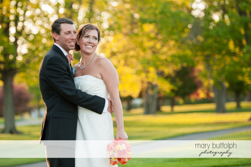 Groom embraces the bride in the garden at Skaneateles Country Club Wedding