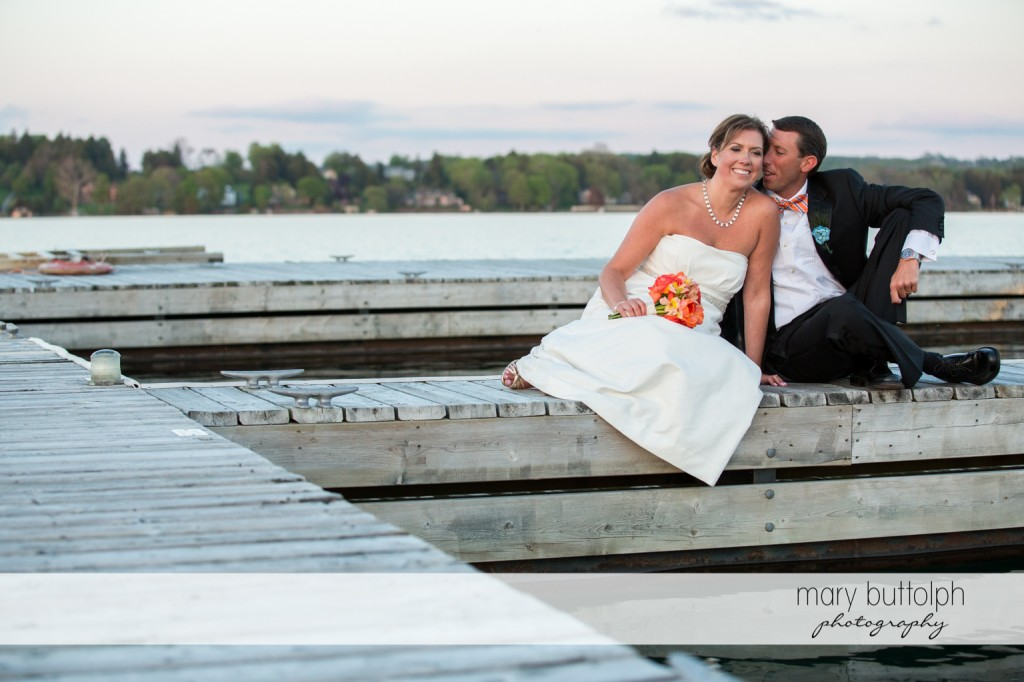Couple sit on the docks at Skaneateles Country Club Wedding