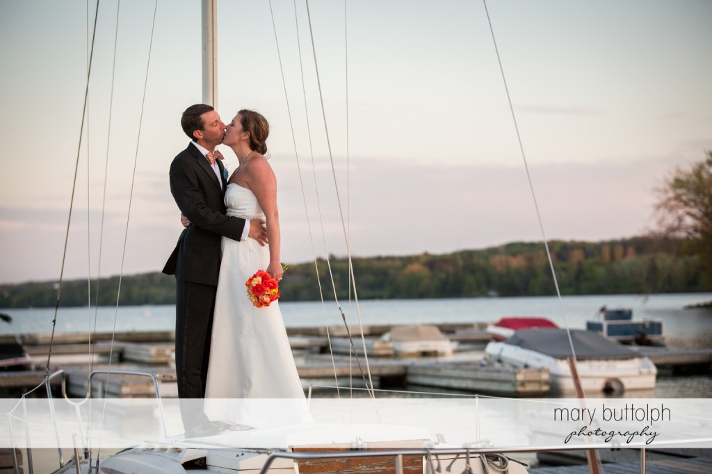Couple kiss on a sailboat at Skaneateles Country Club Wedding