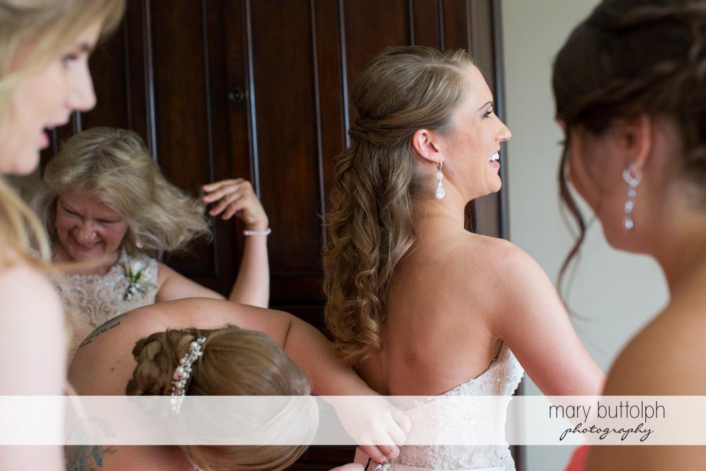 Bridesmaids adjust the bride's wedding dress at the Inns of Aurora Wedding
