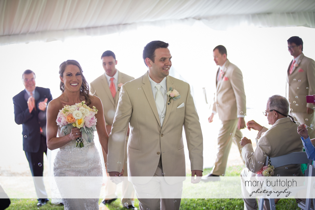 Couple leave the wedding tent at the Inns of Aurora Wedding