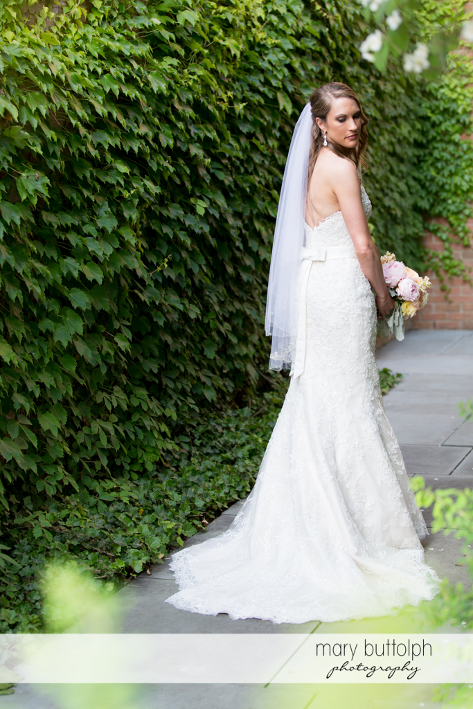 Bride poses in front of a wall of plants at the Inns of Aurora Wedding