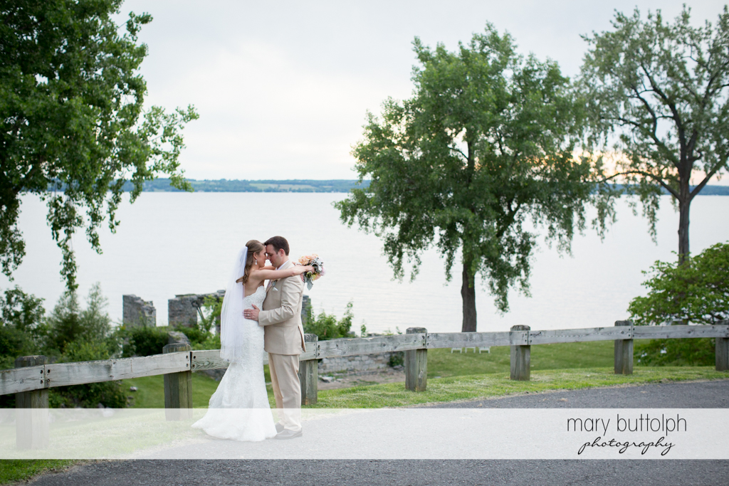 Couple embrace in front of the lake at the Inns of Aurora Wedding